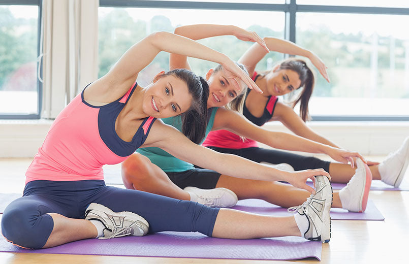 three-smiling-woman-doing-stretching-pilate-exercises-in-fitness-studio
