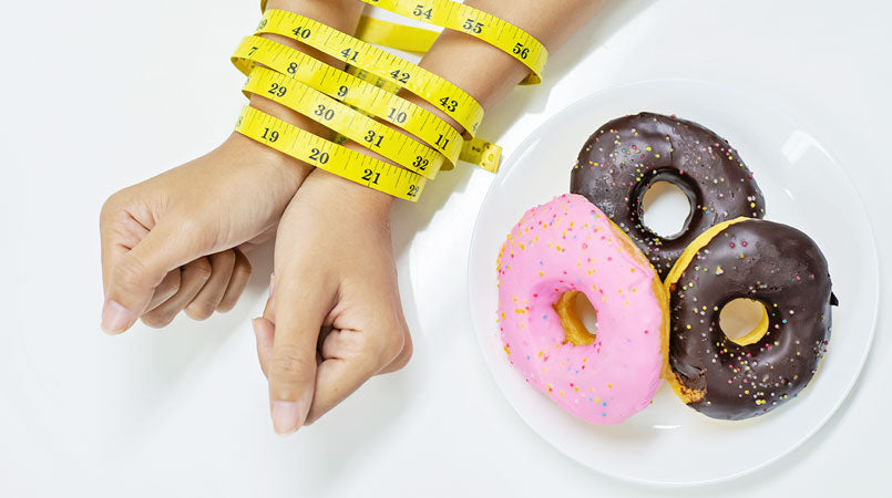 top-view-two-hands-young-woman-been-tied-by-measuring-tape-avoiding-doughnuts