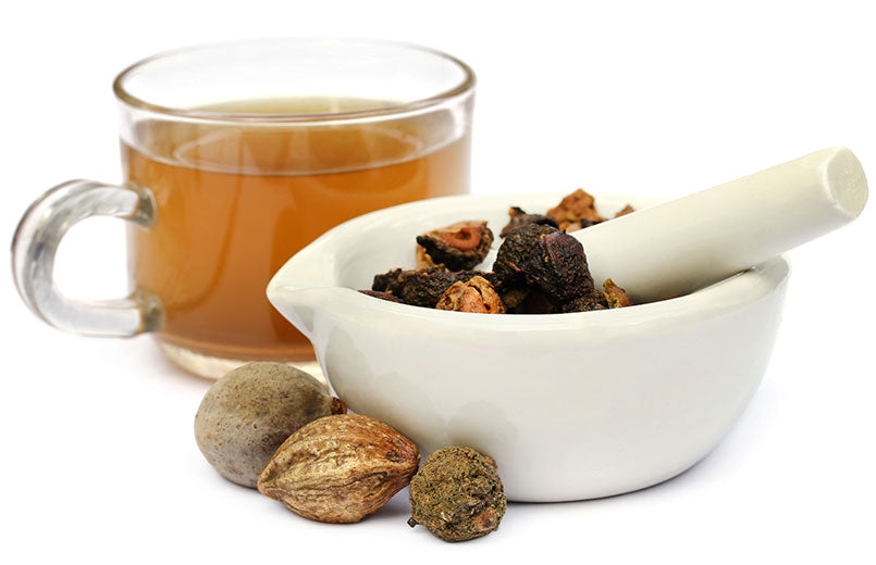 triphala-combination-of-ayurvedic-fruits-cup-of-tea-and-bowl-isolated-on-white-background