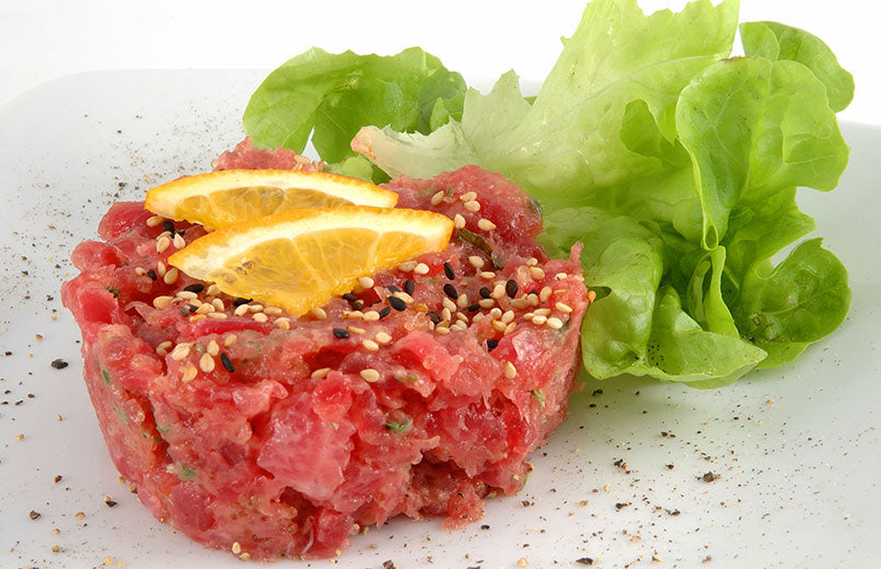 tuna-tartare-sprinkled-with-sesame-seeds-with-lemon-slice-and-lettuce-leaf-on-white-plate