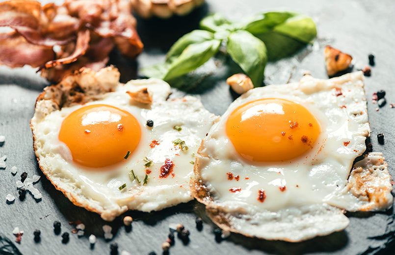 two-fried-eggs-with-slices-of-bacon-in-the-background