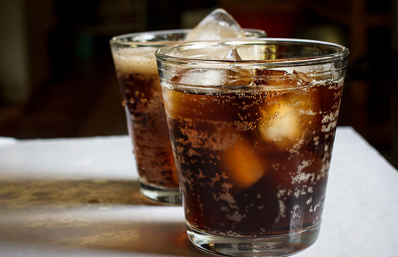 two-glasses-of-cola-on-a-white-table-close-view