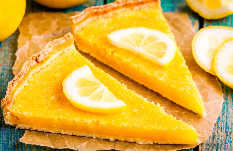two-pieces-of-lemon-tart-with-slice-of-lemons-closeup-on-rustic-blue-table