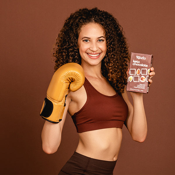 a girl holding a box of keto dark chocolate