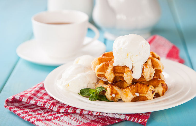 waffle-with-ice-cream-on-top-on-a-white-plate-with-tea-cup-in-the-background-on-a-blue-wooden-table