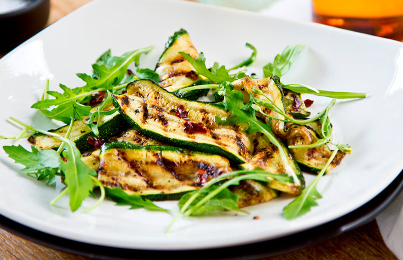 white-plate-with-fried-zucchini-and-arugula-salad