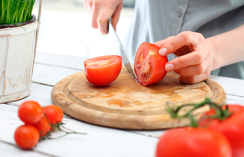 woman-cutting-a-tomato-in-half-with-a-kitchen-knife-on-a-wooden-board