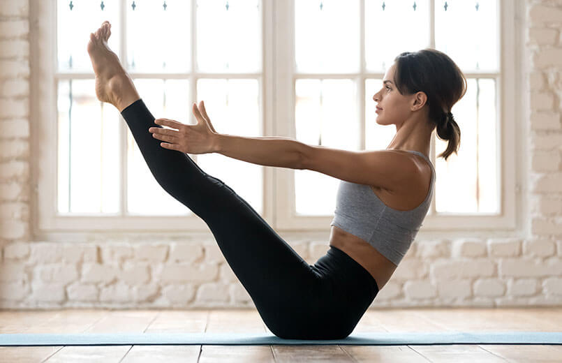 woman-doing-Paripurna-Navasana-yoga-pose-on-a-matresse-in-a-gym