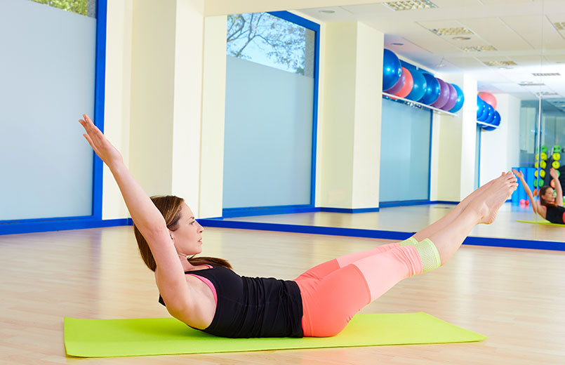 woman-doing-double-leg-stretch-exercise-workout-at-gym-indoor