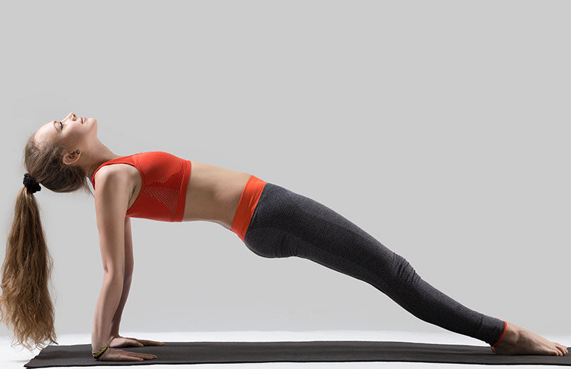 woman-doing-reverse-plank-exercise-on-a-mat