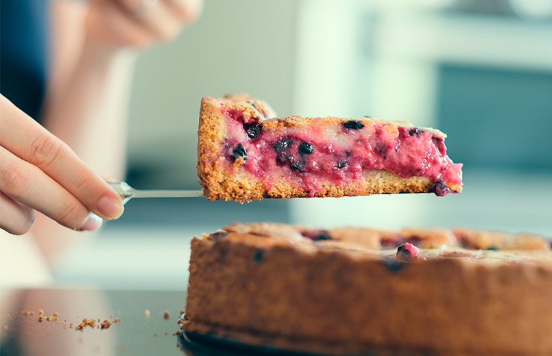 woman-hand-holding-berry-homemade-pie-slice-with-raspberries-and-blueberries