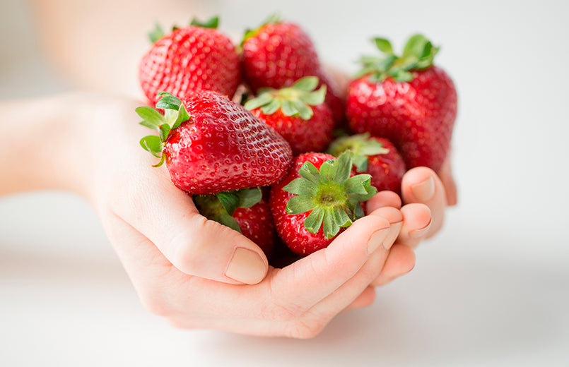 woman-hands-holding-strawberries-on-a-white-background