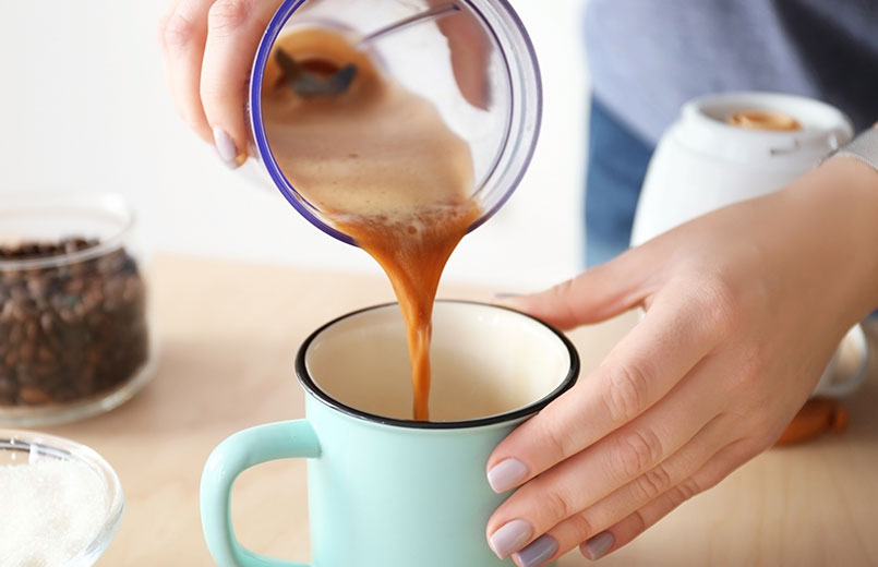 woman-pouring-coffee-with-butter-into-mug-closeup