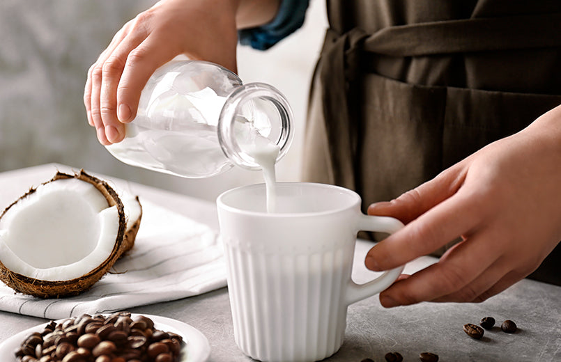 woman-pouring-milk-in-coffee-with-coconut-and-coffee-beans-on-a-table-ketogenic-diet-concept