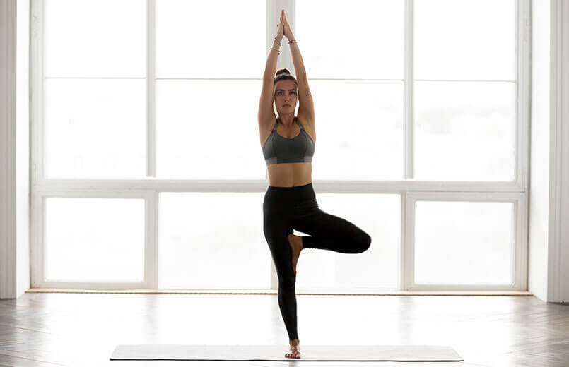 woman-practicing-yoga-Vrksasana-pose-in-front-of-a-window-in-a-gym