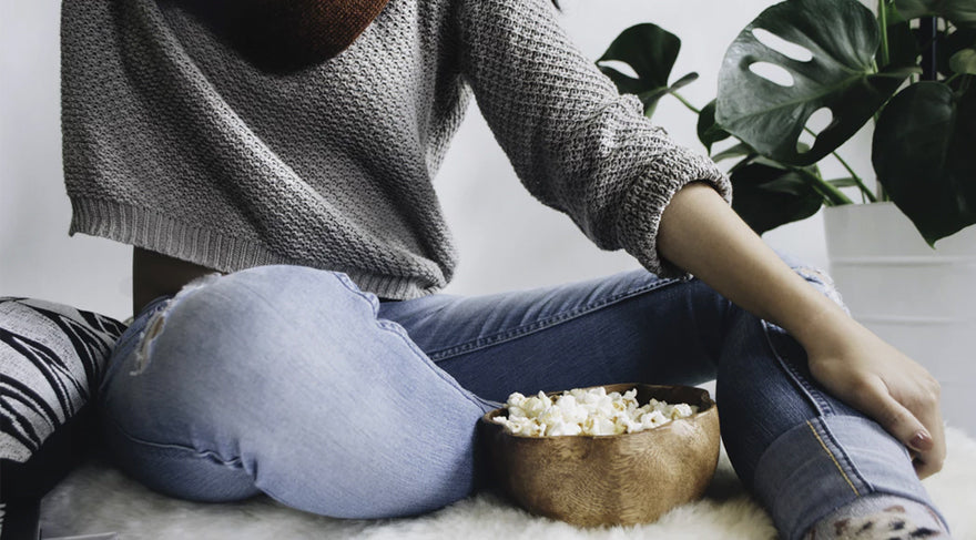 woman-sitting-on-a-couch-with-a-bowl-of-popcorn