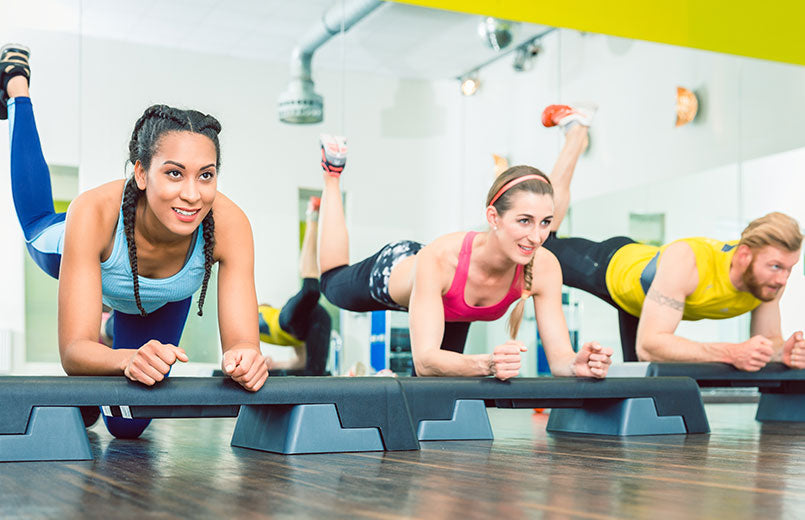 women-and-man-exercising-a-plank-variation-with-raised-leg-at-gym-club