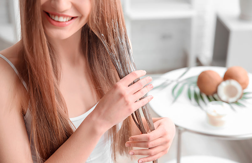 young-woman-applying-coconut-oil-onto-hair-at-home