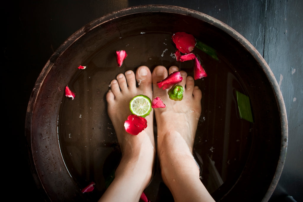 Bare feet in foot bath with flower petals and lime
