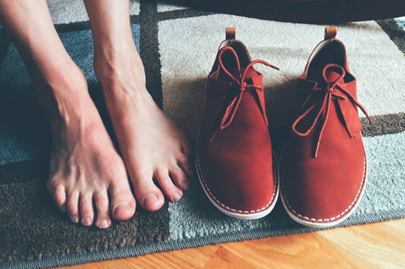 Bare feet on rug next to red shoes