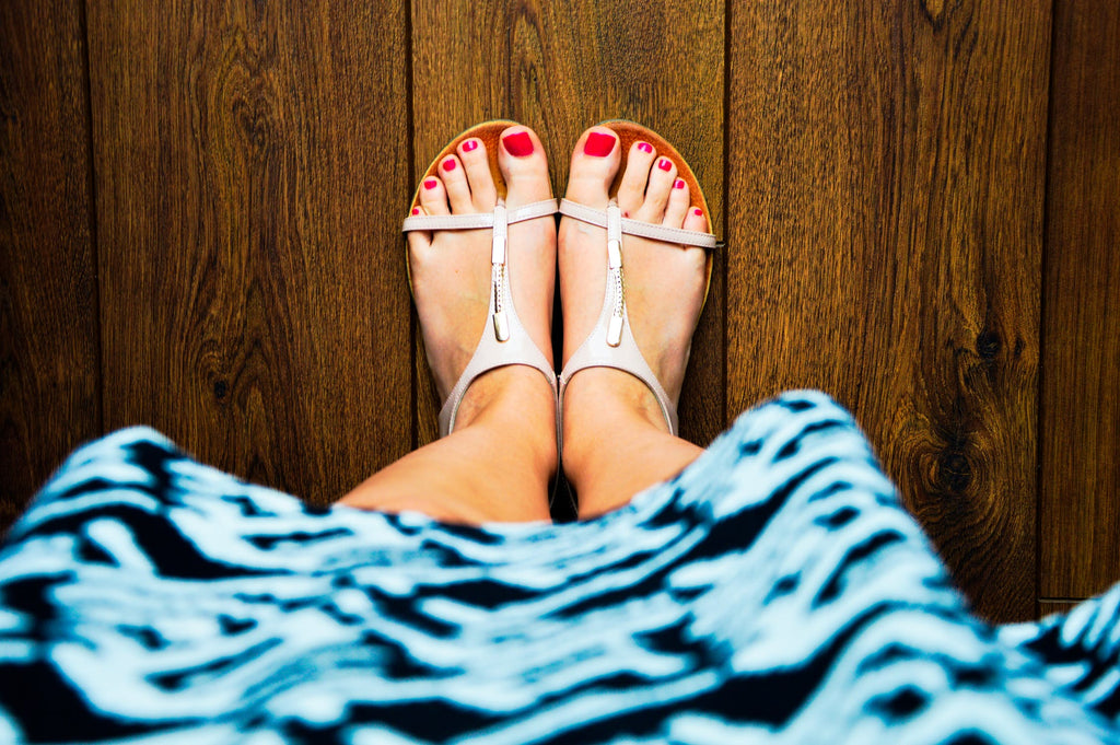Woman's feet with red toenails and white sandals