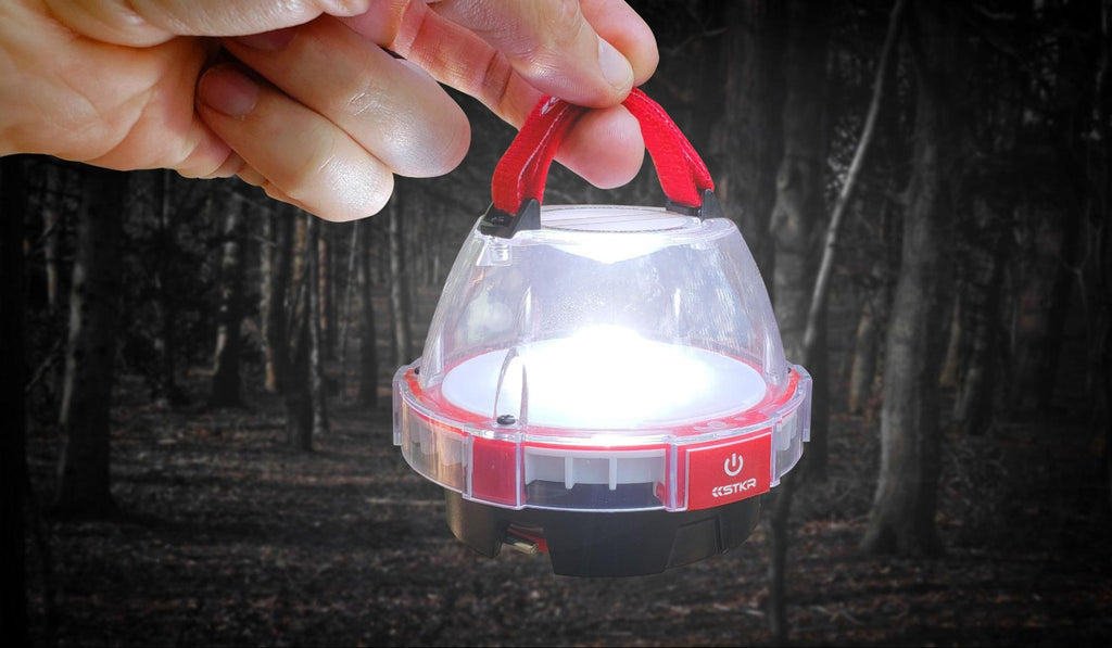 illumidome mini lantern by STKR held up by a hand forest tress in bg