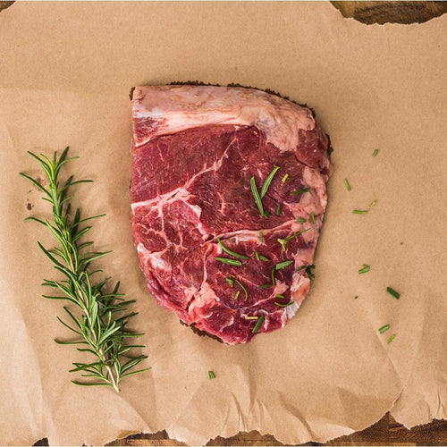 Uncooked Sirloin steak with herbs and brown packaging paper