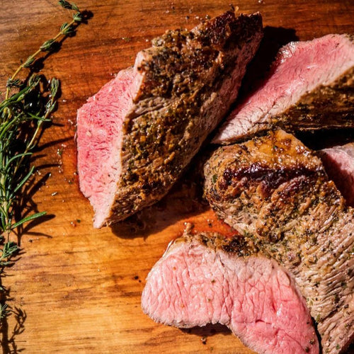 Cooked tri tip beef on a wooden cutting board