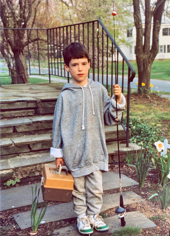 young boy walking down steps with a fishing rod
