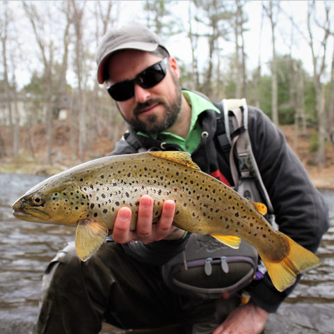 man holding up a trout fish on a lake during trout season