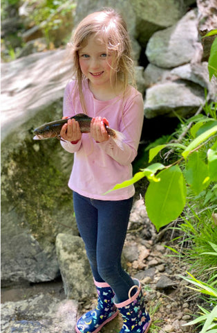 young girl in a pink shirt, jeans, and rain boots holding up a medium sized trout in the woods with green leave on the right