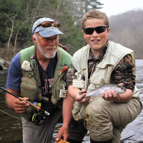 older man on left and young boy on right in fishing outfits on a river. young boy holds up a small trout fish. older man smiles at young boy.