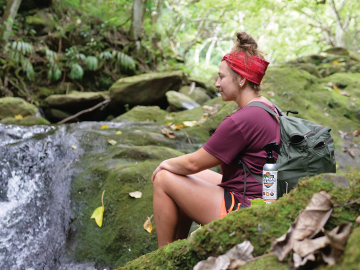 woman sitting next to waterfall in hawaii with ranger ready picaridin (icaridin) mosquito and tick repellent