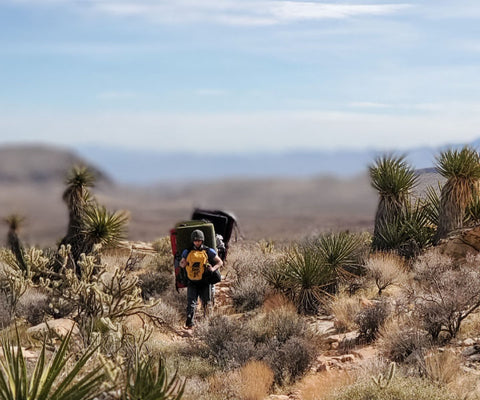 person-with-rock-climbing-matts-hiking-through-the-desert