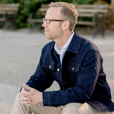 Man sitting on the steps at the park wearing an dark blue denim jean jacket and khaki pants