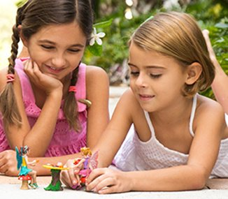 Two girls playing with fairy toys