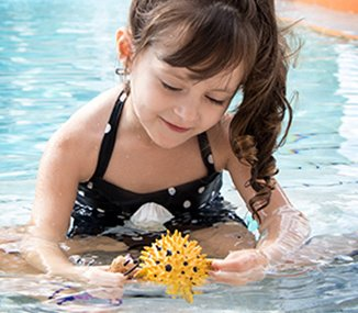 Girl playing with a sea creature toy in a pool