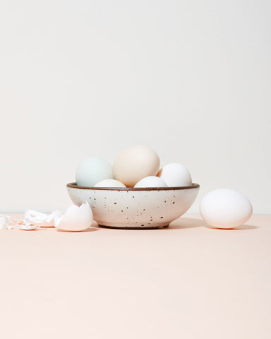 An East Fork Pottery bowl in Eggshell filled with pastel blue, yellow, and white eggs.
