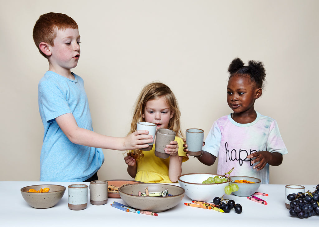 Three young children stand around a table having their own party with East Fork Potter's Juice Cups