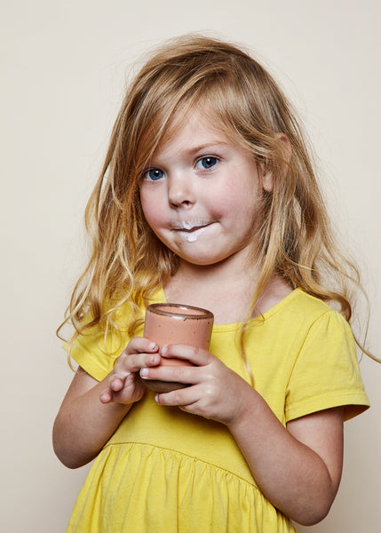 A young girl holds the Toddler Cup by East Fork Pottery, looking into the camera with a milk mustache.