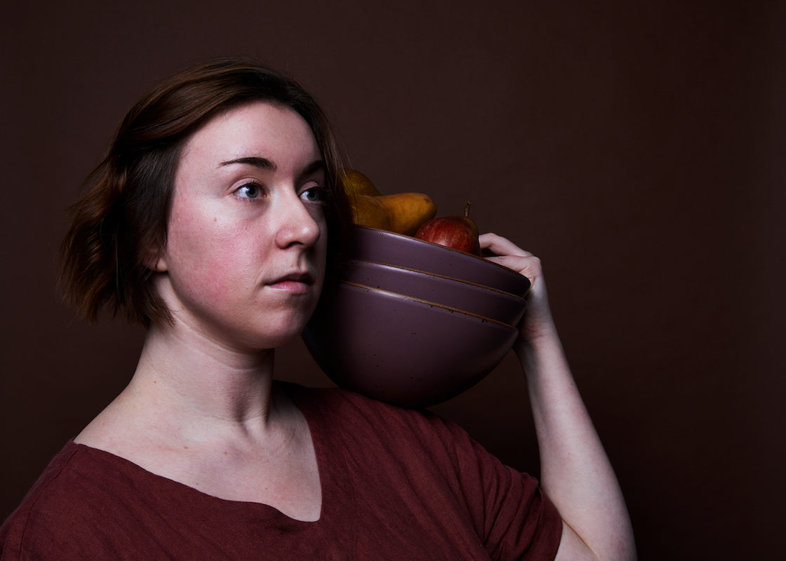 A woman stares into the distance holding a stack of bowls on her shoulder.