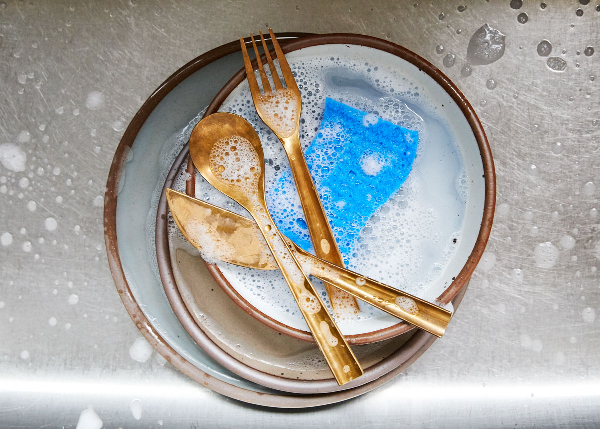 brass flatware in the sink with sudsy water