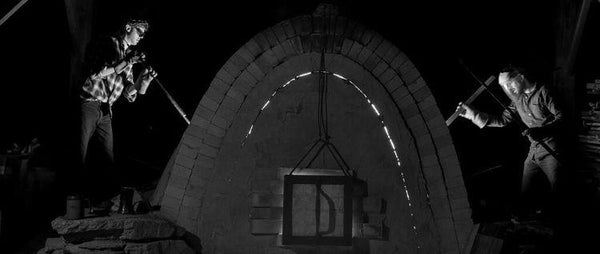 A black and white shot of firing the gas kiln at night.