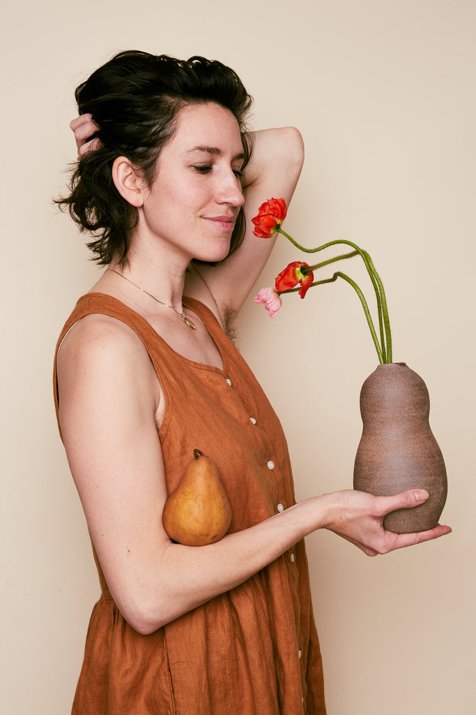 Connie sniffs poppies from the Large Contour Vase in Mars while holding a pear.  Made in the USA by East Fork Pottery.