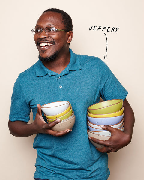 A happy young man in a blue polo holds stacks of colorful pottery.