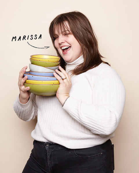 A happy, laughing woman holds a stack of colorful pottery made in Asheville, NC