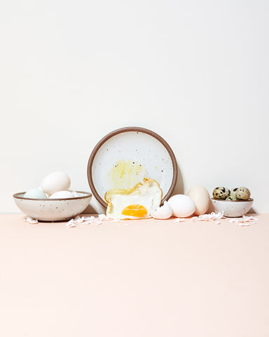 A plate and bowls by East Fork Pottery, glazed in a creamy white called Eggshell, filled with eggs and an over easy egg.