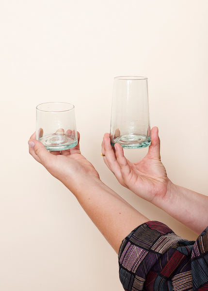 Two hands holding up the medium and large glasses for comparison
