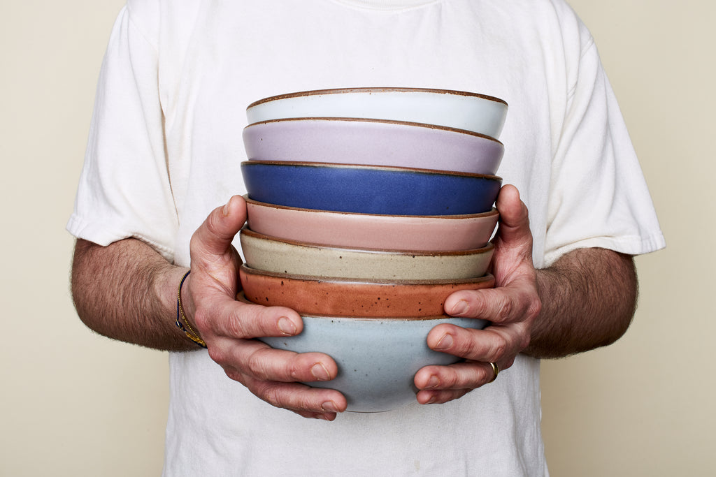 Alex, founder of East Fork Pottery holds a stack of Cereal Bowls in a range of colors