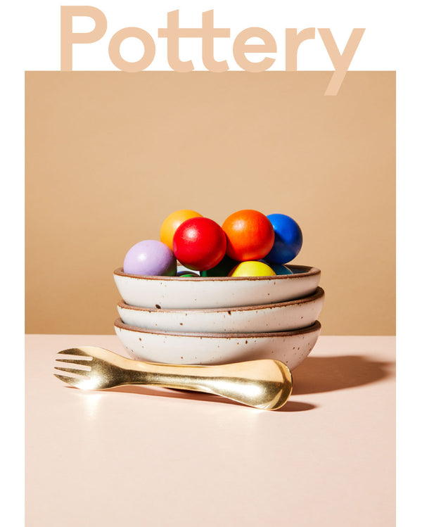 Shop East Fork pottery. A stack of Eggshell bowls with colorful balls and a brass spork
